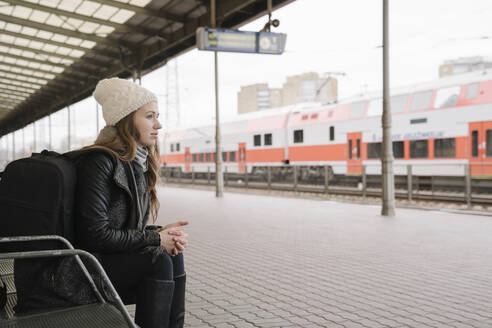 Young woman with backpack waiting on platform, Vilnius, Lithuania - AHSF01597