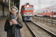 Smiling young woman standing on platform using smartphone and headphones, Vilnius, Lithuania - AHSF01600