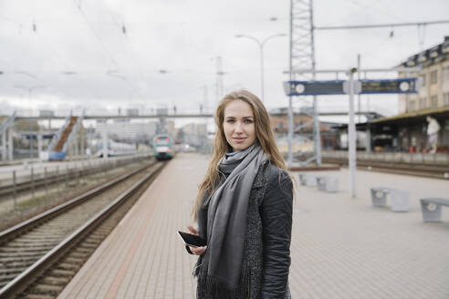 Portrait of smiling young woman with smartphone standing on platform - AHSF01603