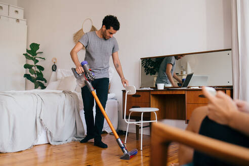 Full length of man cleaning bedroom with vacuum cleaner - MASF14802