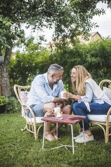 Smiling mature couple talking while sitting in backyard - MASF14932