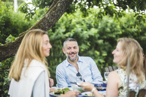 Smiling mature man looking at female friends while enjoying garden party during weekend - MASF14953