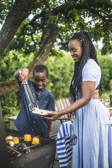 Smiling son assisting mother in preparing food at barbecue grill during backyard party - MASF14986