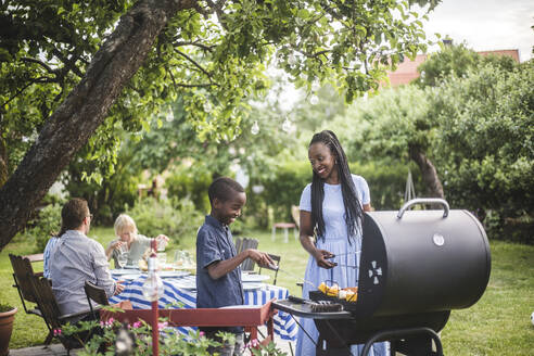 Mother and son preparing food on barbecue grill in yard during weekend party - MASF14992