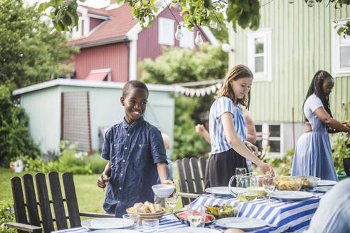 Smiling boy with bowl standing by girl at dining table in backyard party - MASF14998