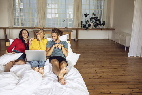 Happy friends relaxing in bed at home watching a movie on laptop - MCF00531
