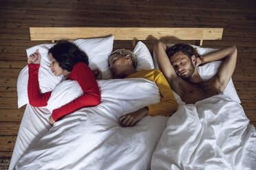 Three friends sleeping in bed at home - MCF00534
