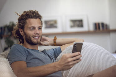 Smiling young man relaxing in beanbag at home using cell phone - MCF00540