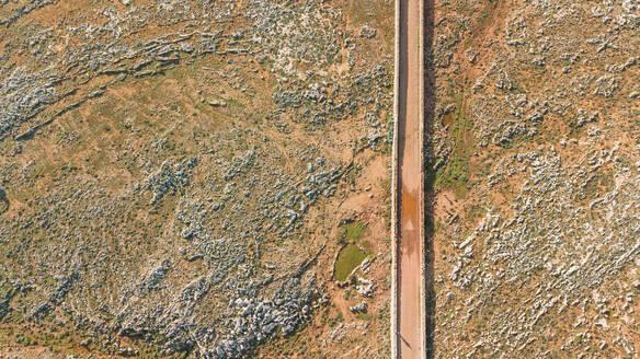 Aerial view of road crossing arid terrain at Balears Island, Spain. - AAEF05867