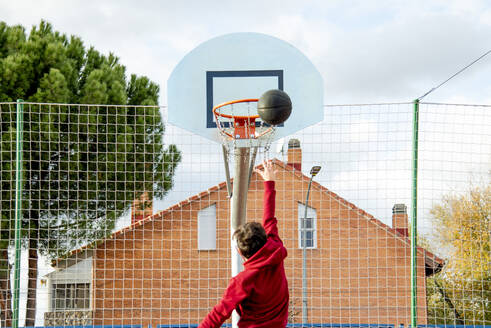 Teenager playing basketball, dunking - CJMF00185