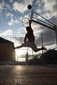 Teenager playing basketball, dunking against the sun - CJMF00191
