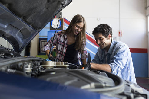 Cheerful man and young woman working together on car repair service and fixing car engine - ABZF02856