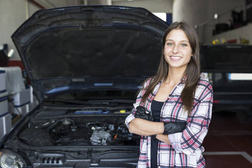 Casual woman in checkered shirt and gloves holding arms crossed and smiling at camera, working in car service - ABZF02862
