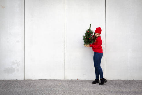 Woman wearing red pullover and wolly hat, holding artificial Christmas tree in front of a wall - HMEF00684