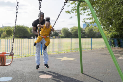 Father with happy daughter swinging on a playground - FBAF01016