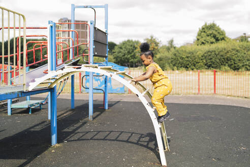 Girl climbing up a ladder on a playground - FBAF01022