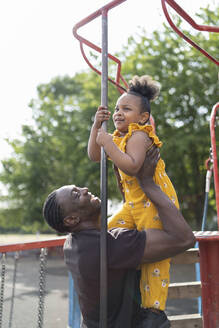 Happy father holding daughter on a playground - FBAF01025