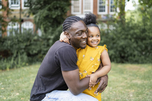 Happy father hugging daughter in a park - FBAF01034