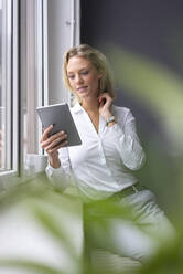 Young businesswoman using tablet at the window - MOEF02650