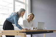 Two businesswomen using laptop at desk in office together - MOEF02662