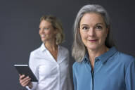 Portrait of confident mature businesswoman with young businesswoman in background - MOEF02677