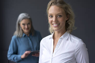 Portrait of smiling young businesswoman with mature businesswoman in background - MOEF02680