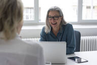Laughing mature businesswoman talking to young businesswoman at desk in office - MOEF02686