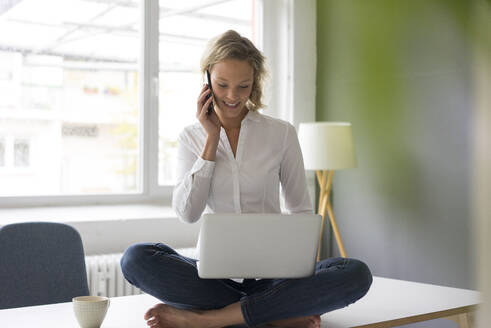 Smiling young businesswoman sitting on desk in office using laptop and cell phone - MOEF02692