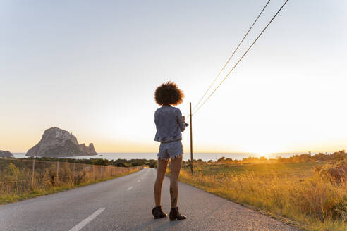 Young woman standing on street at sunset, Ibiza - AFVF04365