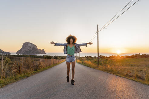 Young woman standing on street at sunset, Ibiza - AFVF04371