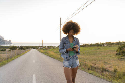 Young woman on a road using smartphone, Ibiza - AFVF04377