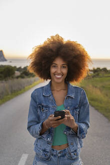 Young woman on a road using smartphone, Ibiza - AFVF04380
