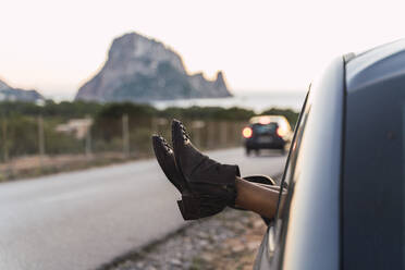 Young woman during road trip, leaning feet out of window - AFVF04383