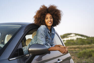Young woman during road trip, leaning out of window - AFVF04386