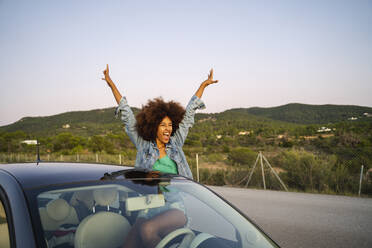 Young woman during road trip with raised arms - AFVF04389