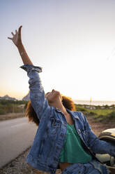 Young woman during road trip with raised arm - AFVF04395