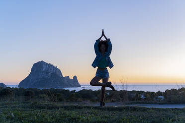 Young woman standing on a meadow doing yoga at sunset, Ibiza - AFVF04401