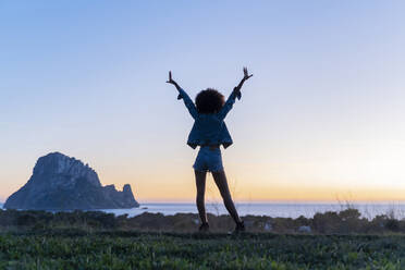 Rear view of young woman standing on a viewpoint with raised arms at sunset, Ibiza - AFVF04404