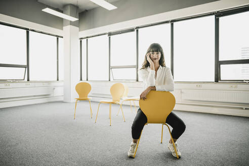 Smiling businesswoman sitting on a chair in an empty office - KNSF06872