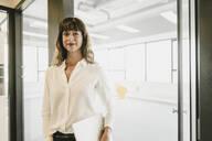 Smiling businesswoman standing in an open office door - KNSF06875