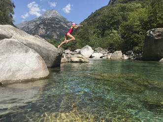 Woman's jump into refreshing mountain river water - GWF06331