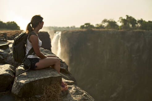 Woman sitting on the top of a rock enjoying the Victoria Falls at sunset, Zimbabwe - VEGF01052