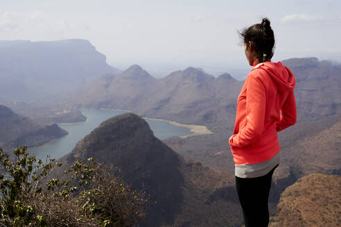 Woman standing on top of a hill enjoying the beautiful landscape below her, Blyde River Canyon, South Africa. - VEGF01061