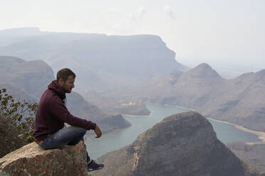 Man sitting on a rock with beautiful landscape as background, Blyde River Canyon, South Africa - VEGF01064