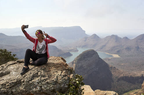 Woman taking a selfie with her cell phone with a beautiful landscape background, Blyde River Canyon, South Africa - VEGF01067