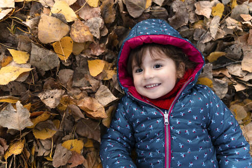 Portrait of happy little girl lying on autumn leaves - GEMF03321