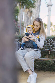 Mother resting with baby boy on a park bench using smartphone - ERRF02236