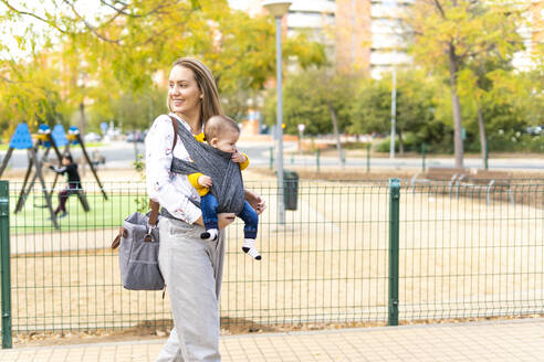 Happy mother walking with baby boy in sling outdoors - ERRF02281
