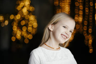 Portrait of happy blond girl at Christmas time - EYAF00736