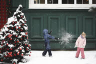 Siblings having a snowball fight at Chrismas time - EYAF00739